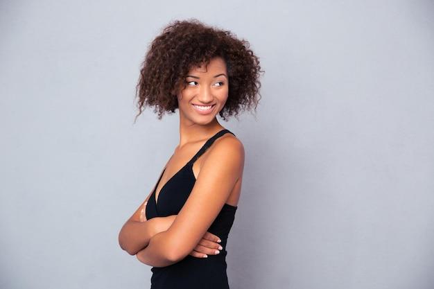 Portret szczęśliwej kobiety z założonymi rękoma stojąc na szarej ścianie i odwracając wzrok