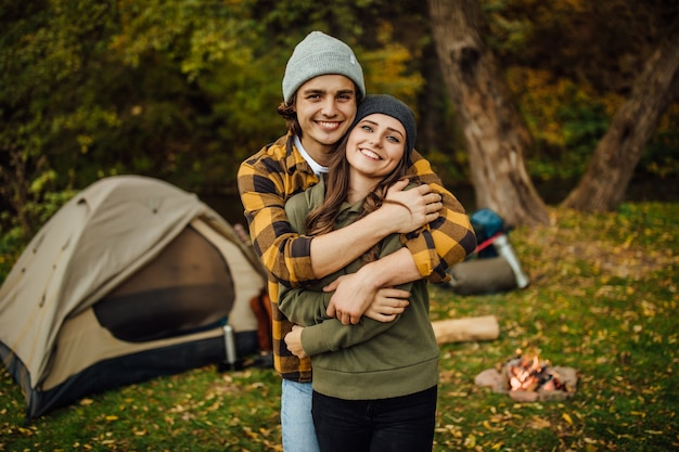 Portret szczęśliwej kochającej się pary turystów w zwykłych ubraniach w lesie w pobliżu namiotu