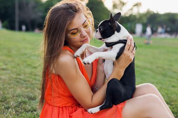 Portret szczęśliwej ładnej kobiety siedzącej na trawie w letnim parku, trzymającej boston terriera, uśmiechniętego pozytywnego nastroju, noszącej pomarańczową sukienkę, modny styl, okulary przeciwsłoneczne, bawiąc się ze zwierzakiem