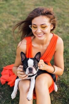 Portret szczęśliwej ładnej kobiety siedzącej na trawie w letnim parku, trzymającej boston terriera, uśmiechniętego pozytywnego nastroju, noszącej pomarańczową sukienkę, modny styl, okulary przeciwsłoneczne, zabawa ze zwierzakiem, zabawa