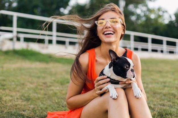 Portret szczęśliwej ładnej kobiety siedzącej na trawie w letnim parku, trzymającej psa boston terriera, uśmiechającej się pozytywnie, bawiącej się zwierzakiem