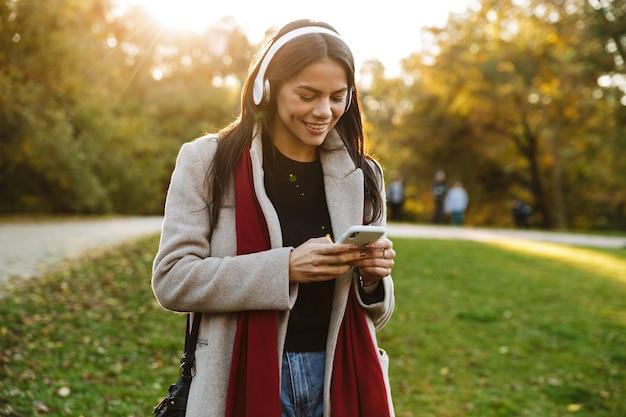 Portret szczęśliwej ładnej kobiety w płaszczu, słuchającej muzyki przez słuchawki i używającej telefonu komórkowego podczas spaceru w jesiennym parku