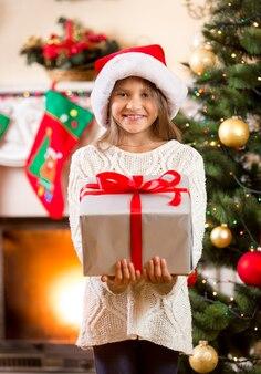 Portret szczęśliwej małej dziewczynki trzymającej duże pudełko na prezent świąteczny