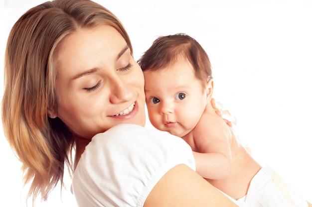 Portret szczęśliwej małej uśmiechniętej dziewczyny trzymanej w rękach troskliwej matki