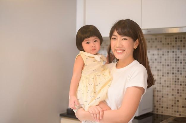 Portret szczęśliwej mamy i córki w kuchni w domu