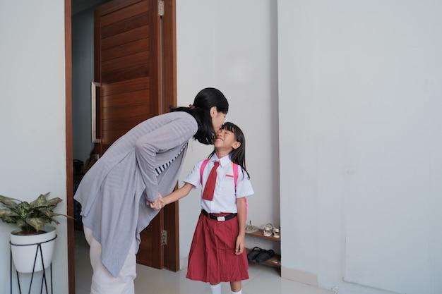 Portret szczęśliwej matki całuje jej policzek dziecka rano w domu przed dniem szkolnym