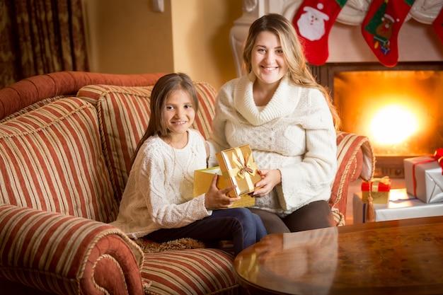 Portret szczęśliwej matki i córki pozujących przy kominku z pudełkiem na boże narodzenie