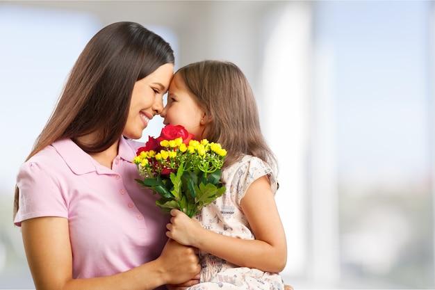 Portret szczęśliwej matki i córki trzymających kwiaty