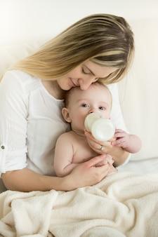 Portret szczęśliwej matki i jej dziecka jedzących z butelki