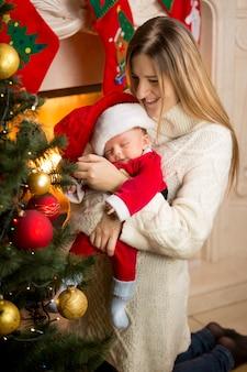 Portret szczęśliwej matki i synka dekorujących choinkę