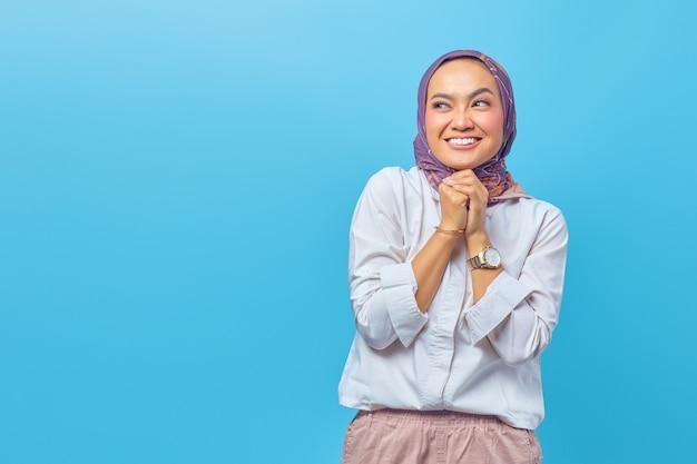 Portret szczęśliwej młodej azjatyckiej kobiety patrzącej radośnie na bok ze składaną podniesioną ręką