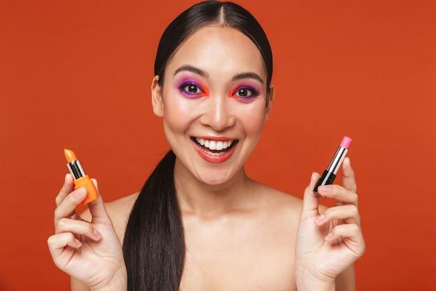 Portret szczęśliwej młodej azjatyckiej kobiety topless z brunetką w jasnym makijażu, stojącej odizolowanej na czerwono, wybierającej spośród dwóch różnych szminek