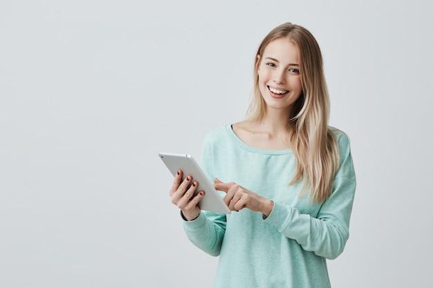 Portret szczęśliwej młodej blondynki biznesowa kobieta w przypadkowych ubraniach używać pastylkę