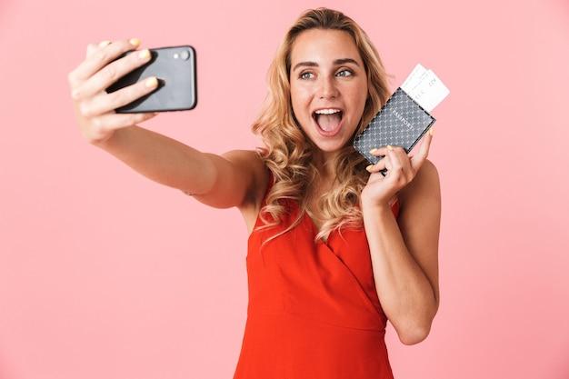 Portret szczęśliwej młodej blondynki turystki pozuje na białym tle nad różową ścianą rozmawiając przez telefon komórkowy weź selfie trzymając paszport z biletami