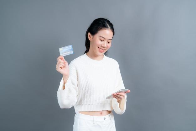 Portret szczęśliwej młodej dziewczyny azjatki pokazującej plastikową kartę kredytową trzymając telefon komórkowy mobile