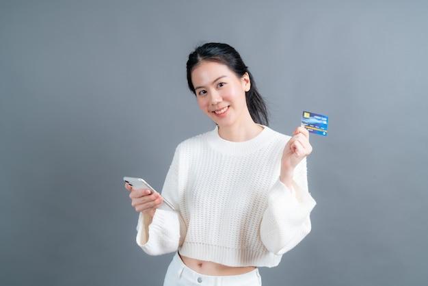 Portret szczęśliwej młodej dziewczyny azjatyckich pokazując plastikową kartę kredytową, trzymając telefon komórkowy na szarej ścianie
