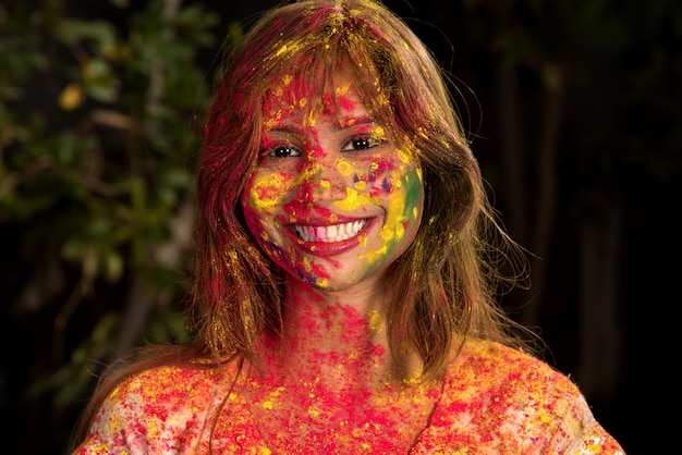 Portret szczęśliwej młodej dziewczyny na festiwalu kolorów holi. dziewczyna pozuje festiwal kolorów i świętuje.