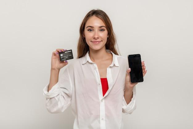 Portret szczęśliwej młodej dziewczyny pokazującej kartę kredytową, trzymając telefon komórkowy z czarnym ekranem