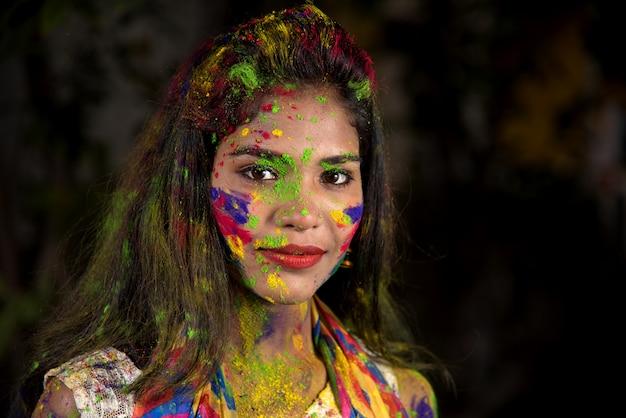 Portret szczęśliwej młodej dziewczyny z kolorową twarzą z okazji festiwalu kolorów holi.