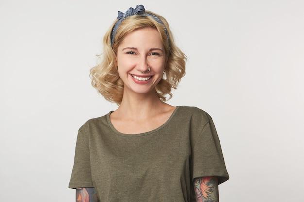 Portret szczęśliwej młodej dziewczyny ze związanymi włosami i swobodnymi ubraniami na szaro