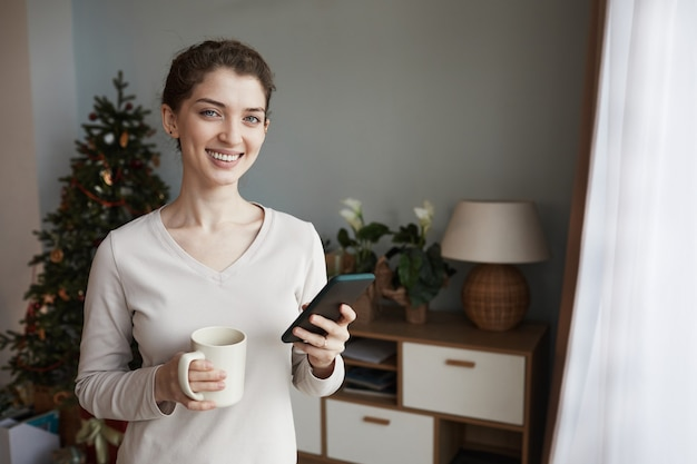 Portret szczęśliwej młodej kaukaskiej kobiety w swetrze stojącej z kubkiem w pokoju z choinką i...