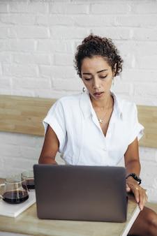 Portret szczęśliwej młodej kobiety afryki, relaks w kawiarni na świeżym powietrzu i za pomocą laptopa. praca zdalna
