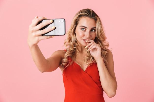 Portret szczęśliwej młodej kobiety blondynka pozuje na białym tle nad różową ścianą rozmawiając przez telefon komórkowy, weź selfie
