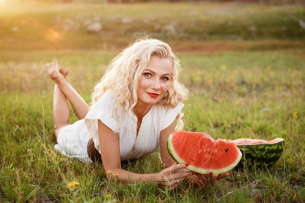 Portret szczęśliwej młodej kobiety cieszącej się i jedzącej arbuza na zewnątrz slow life lato styl życia koncepcja szczęście radość wakacje dzień niepodległości