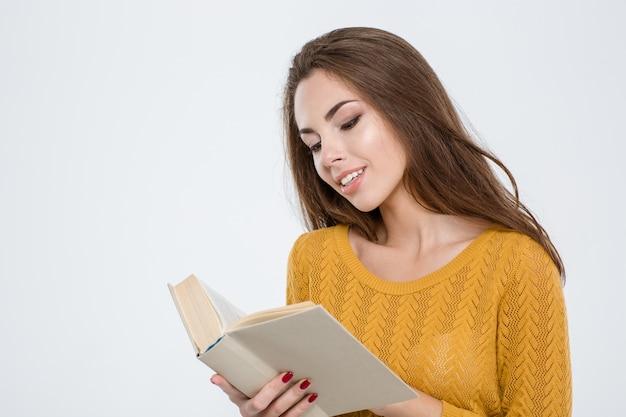 Portret szczęśliwej młodej kobiety czytającej książkę na białym tle