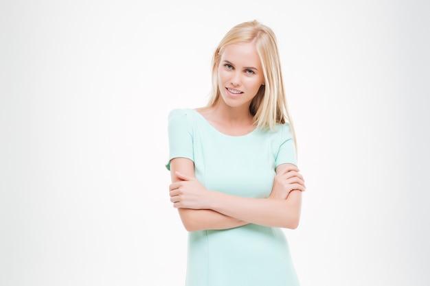 Portret szczęśliwej młodej kobiety patrzącej z przodu z rękami skrzyżowanymi na białym tle nad białą ścianą