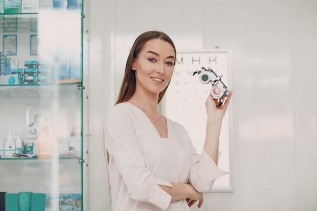 Portret szczęśliwej młodej kobiety podczas badania wzroku u okulisty optyka