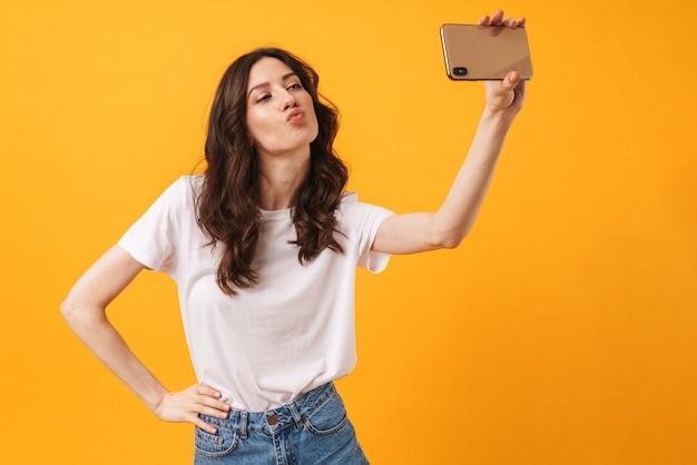 Portret szczęśliwej młodej kobiety pozuje na białym tle nad żółtą ścianą, weź selfie przez telefon komórkowy, posyłając buziaki