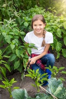 Portret szczęśliwej młodej kobiety pracującej w ogrodzie z kielnią