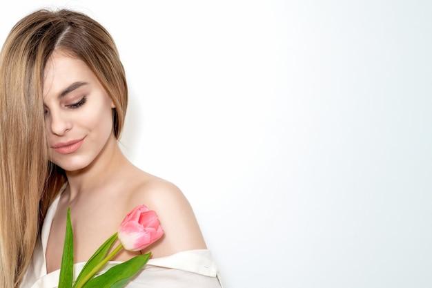 Portret szczęśliwej młodej kobiety rasy kaukaskiej z zamkniętymi oczami i jednym różowym tulipanem na białym tle z miejsca na kopię
