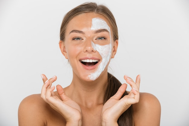 Portret szczęśliwej młodej kobiety topless na białym tle, patrząc z pół twarzy zakrytej białą maską