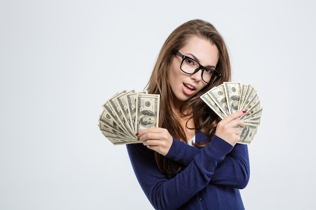 Portret szczęśliwej młodej kobiety trzymającej rachunki dolarowe na białym tle