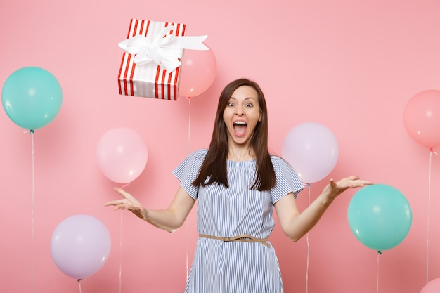 Portret szczęśliwej młodej kobiety w niebieskiej sukience rozkładając ręce rzucając czerwone pudełko z prezentem na pastelowym różowym tle z kolorowymi balonami. urodziny wakacje, ludzie szczere emocje.