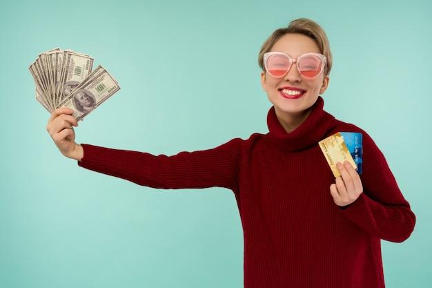 Portret szczęśliwej młodej kobiety w różowych okularach przeciwsłonecznych, trzymając w ręku kartę kredytową i pieniądze, uśmiechając się i patrząc na kamerę na odosobnionym niebieskim tle, czując się pozytywnie i ciesząc się
