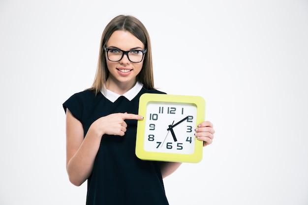 Portret szczęśliwej młodej kobiety wskazujący palec na dużym zegarze na białym tle