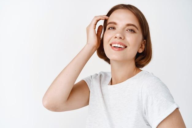 Portret szczęśliwej młodej kobiety z naturalnym jasnym makijażem twarzy, dotykającą fryzury i uśmiechniętą, stojącą w koszulce na białej ścianie