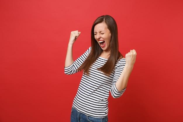 Portret szczęśliwej młodej kobiety z zamkniętymi oczami w pasiastych ubraniach robi zwycięski gest krzyczy