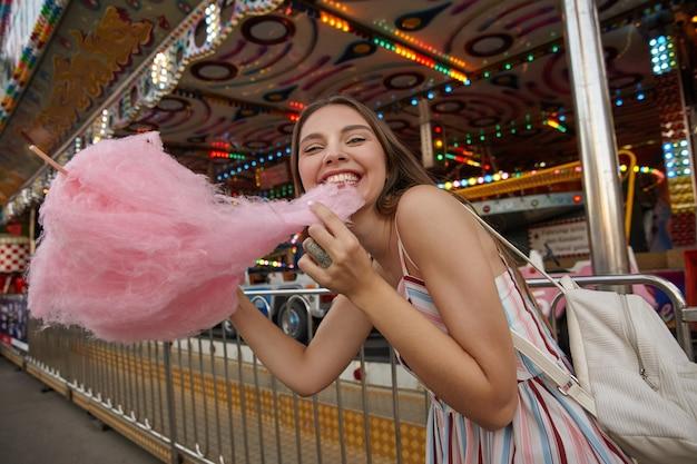 Portret szczęśliwej młodej ładnej kobiety o brązowych włosach w lekkiej letniej sukience, spacerującej po parku rozrywki w ciepły dzień, trzymającej watę cukrową w dłoni i ciągnącej ją zębami