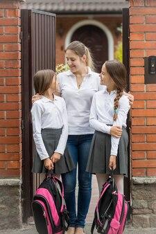 Portret szczęśliwej młodej matki patrzącej na swoje córki wychodzące do szkoły