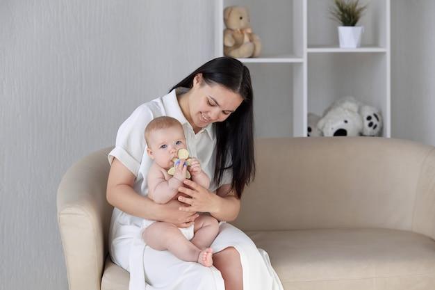 Portret szczęśliwej młodej matki przytulającej swojego synka gryzącego zabawkę