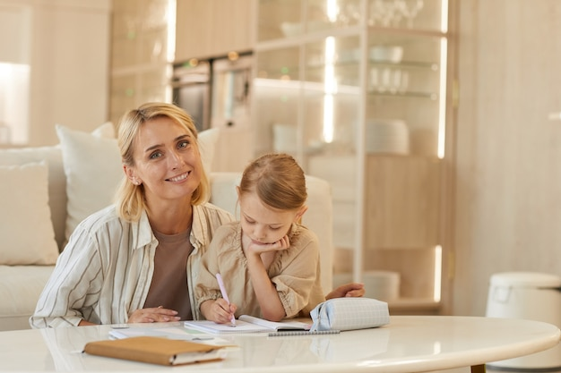 Portret szczęśliwej młodej matki uśmiechając się pomagając ślicznej dziewczynki, opierając się na nauce w domu