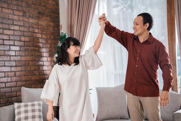 Portret szczęśliwej młodej pary azjatyckich cieszyć się razem, tańcząc w boże narodzenie w domu