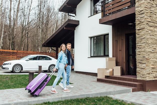 Portret szczęśliwej młodej pary przytulanie przed ich nową, luksusową willą domową.