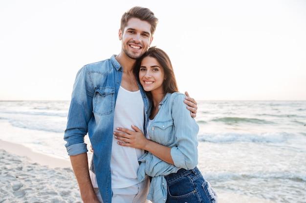Portret szczęśliwej młodej pary stojącej i przytulającej się na plaży