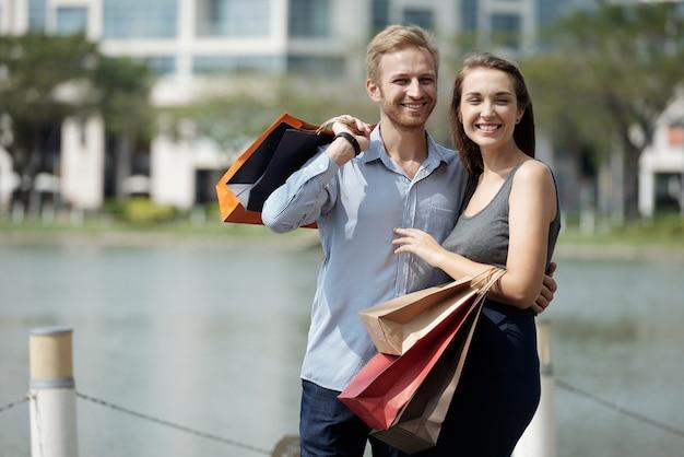 Portret szczęśliwej młodej pary zakochanej trzymającej torby na zakupy, stojąc na zewnątrz i uśmiechając się do c...