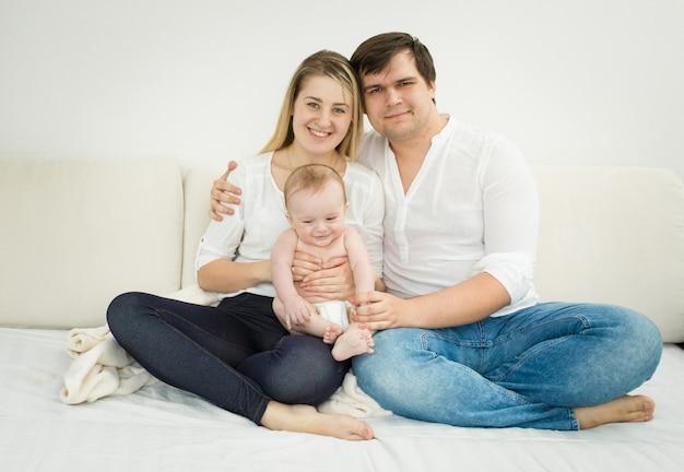 Portret szczęśliwej młodej rodziny pozuje z synkiem na łóżku